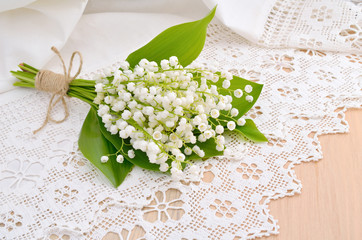 Bouquet of lilies of the valley on a lacy cloth.