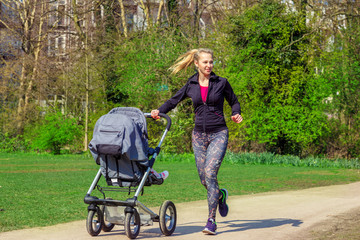 Smiling woman pushing baby buggy