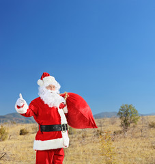 Santa holding a bag of presents and hitchhiking