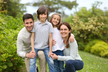Portrait of cheerful family standing in home garden