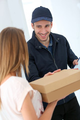 Smiling delivery man giving cardbox to customer