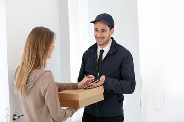 Woman signing receipt of package delivery