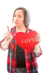 Young woman holding heart shape with pointing