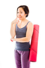 Young woman carrying exercise mat biting nail