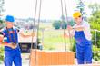 Kranführer liefert Palette Backsteine auf Baustelle