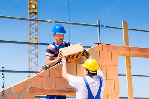 Maurer mauern Wand auf Baustelle - 64579145