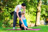 Fototapety Junge Frau macht Joga  mit Trainer im Freien