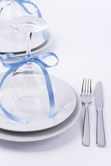 Festive table set with glasses and silverware on white backgroun