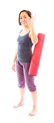 Young woman carrying exercise mat showing ok sign