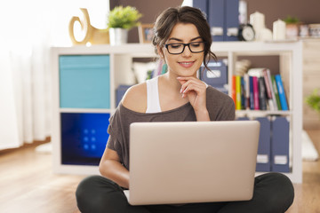 Smiling woman using laptop on floor at home