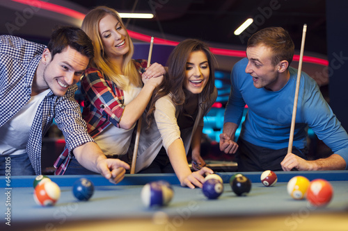 Group of young friends playing billiard - 64582105