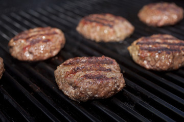 Hamburger patties cooking on a grill.