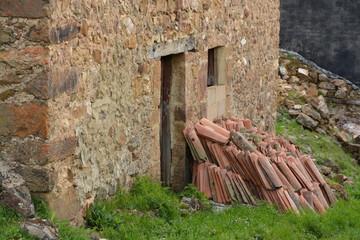 monton de tejas apiladas contra una casa de piedra