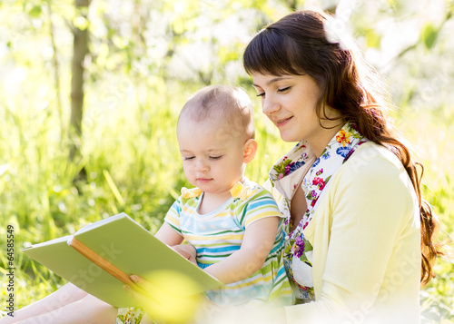 happy mother reading a book to child outdoors