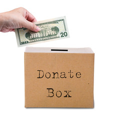 Human hand putting money in brown donate box. Concept of savings