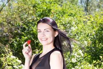 Attraktives Maedchen mit Erdbeere im Wald
