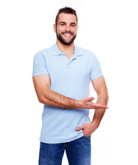 Happy young man in polo shirt showing empty copyspace