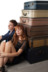 Couple sitting near suitcases