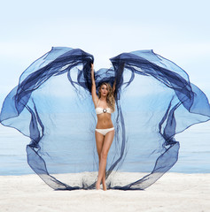 Beautiful woman on the beach dancing with a blowing silk