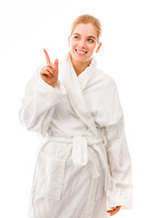 Young woman standing in bathrobe and pointing upward