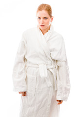 Young woman standing in bathrobe and looking serious