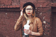 stylish woman with coffee on brick wall background