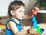 cute boy playing with toy blocks and bricks