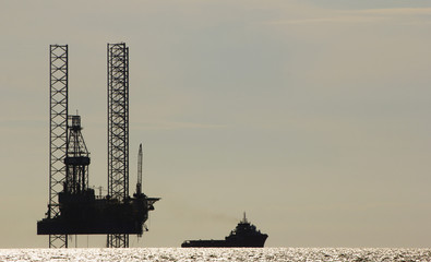 Silhouette of an offshore drilling rig and supply vessel