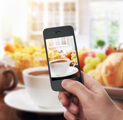 Hand with smartphone taking food photo of fresh healthy breakfas