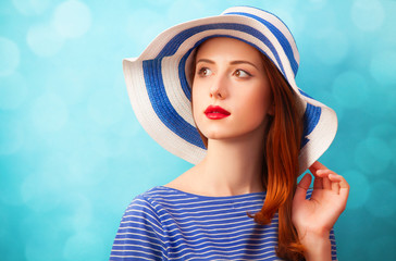 Redhead girl in hat on blue background.
