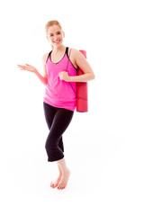 Young woman carrying exercise mat and showing something