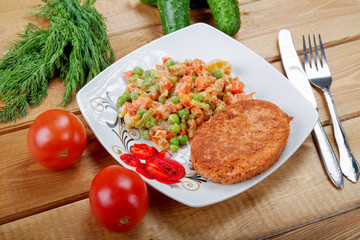 Fish cutlet with vegetables on a rural table
