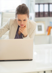 Thoughtful business woman working on laptop in office