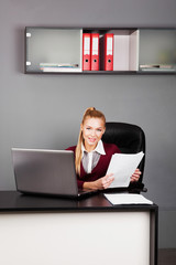 Young businesswoman sitting at workplace and reading paper in