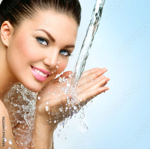 Beautiful smiling girl under splash of water