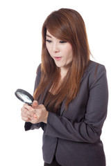 Asian businesswoman surprised use magnifying glass looking down