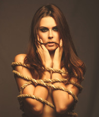 brunette woman bound with rope prisoner in jeans on a gray backg