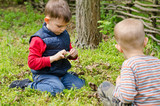 Two small boys lighting a fire in woodland