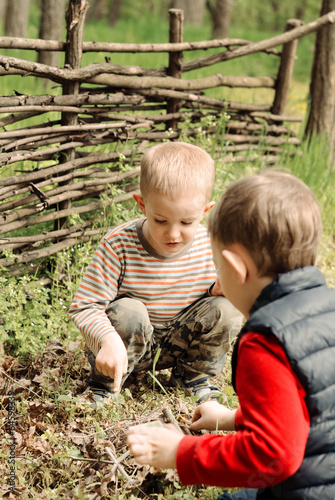 Two young boys discussing lighting a campfire