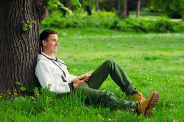 Young happy man reading book in the nature