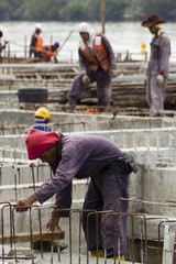 Workers make reinforcements for concrete foundations