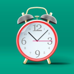 Red vintage alarm clock on green background