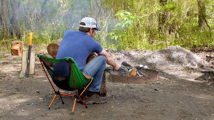 Man with Hat Roasting Marshmallows on a Campfire (Wide)