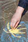 girl paints sun in blue sky with chalks outdoors poster
