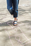 girl hoping in hopscotch outdoors poster
