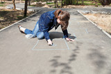 girl drawing hopscotch outdoors poster