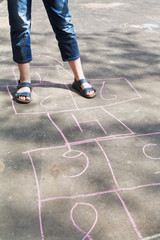 girl playing in hopscotch outdoors
