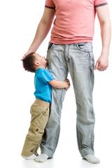 Kid boy hugging his father's leg