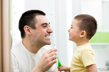 child boy and his dad cleaning teeth in bathroom