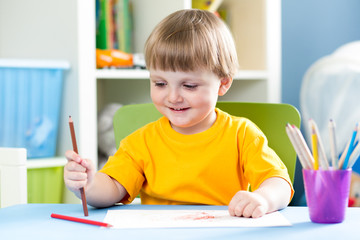 kid boy drawing with pencils at home